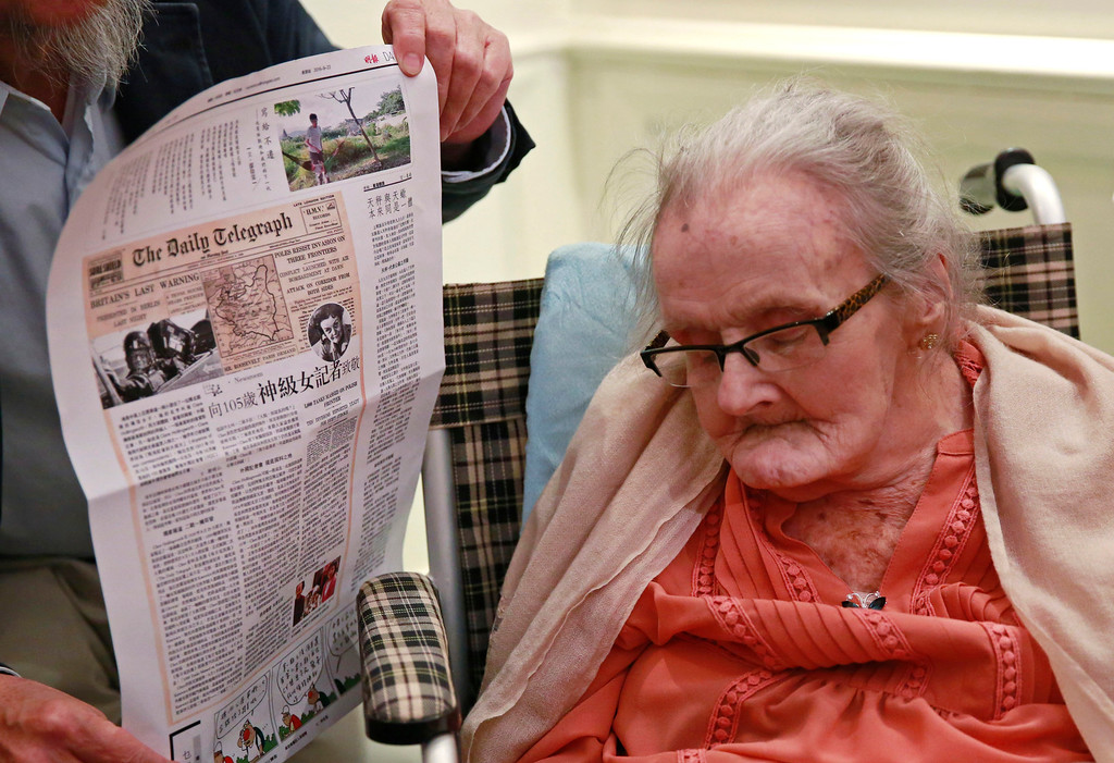 . A guest displays a newspaper copy with Clare Hollingworth, right, a British former longtime foreign correspondent at her birthday party at Hong Kong\'s Foreign Correspondents\' Club, Monday, Oct. 10, 2016. Hollingworth spent decades covering wars and conflicts in Europe, the Middle East and Asia, starting with her scoop in August 1939 about the outbreak of the Second World War when she reported for Britain\'s Daily Telegraph on German troops massing on the Polish border. She died Jan. 10 at age 105. (AP Photo/Kin Cheung)