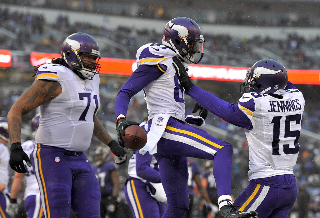 . Minnesota Vikings wide receiver Jerome Simpson, center, celebrates his touchdown with teammates Phil Loadholt, left, and Greg Jennings in the second half of an NFL football game against the Baltimore Ravens, Sunday, Dec. 8, 2013, in Baltimore. (AP Photo/Gail Burton)