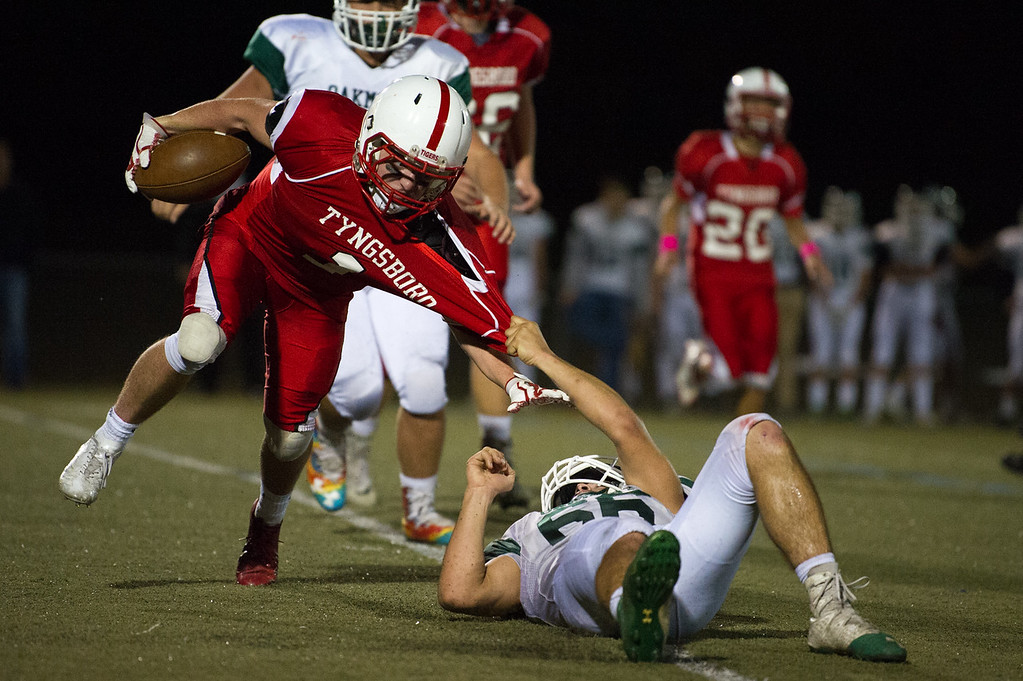 . Tyngsboro junior Evan Robson (left) is pulled down by Oakmont senior Isaiah Williamson during a varsity football game at home on Saturday Oct. 21, 2017.  SENTINEL & ENTERPRISE JEFF PORTER