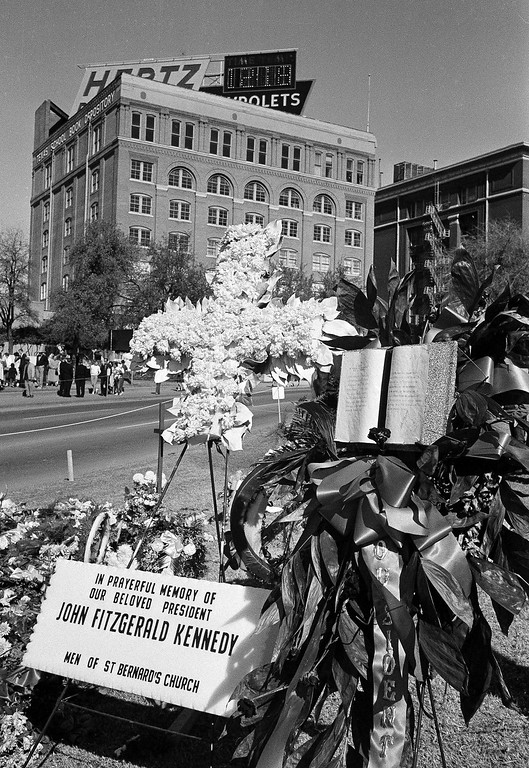 . Flowers mark a spot near where Kennedy was assassined a week after his death. In the background is the Texas School Book Depository, where the assassin fired from the far right window on the second floor from the top. Associated Press file