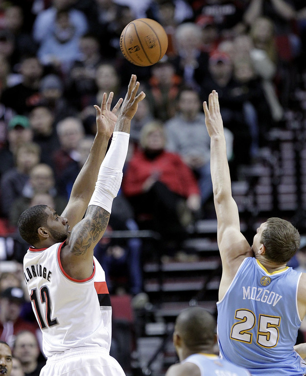 . Portland Trail Blazers forward LaMarcus Aldridge, left, shoots over Denver Nuggets center Timofey Mozgov, from Russia, during the first half of an NBA basketball game in Portland, Ore., Saturday, March 1, 2014. (AP Photo/Don Ryan)