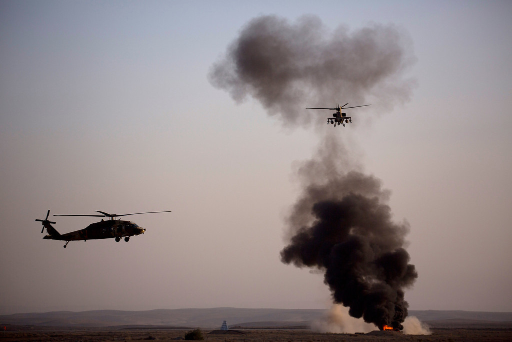 . An Israeli Air Force Blackhawk helicopter, left, and an Israeli air force Apache helicopter perform during an aerobatic display at a graduation ceremony for new pilots in the Hatzerim air force base near the city of Beersheba, southern Israel, Thursday, Dec. 26, 2013. (AP Photo/Ariel Schalit)