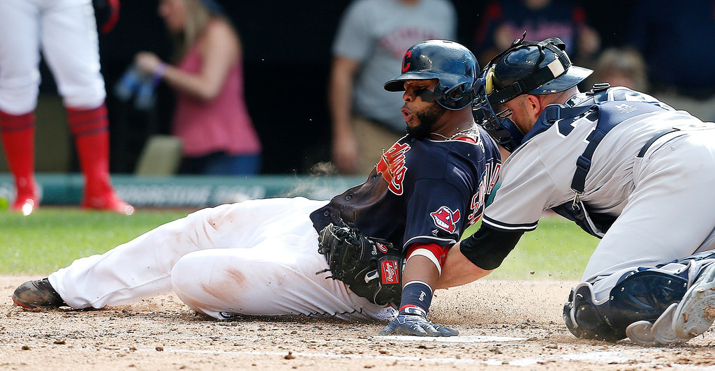 . Cleveland Indians\' Carlos Santana, left, is tagged out at home plate by New York Yankees\' Brian McCann (34) during the third inning of a baseball game Saturday, July 9, 2016, in Cleveland. (AP Photo/Ron Schwane)