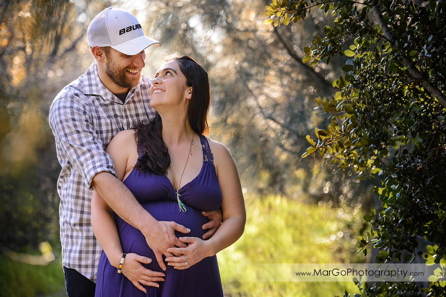 portrait of man in checkered shirt and pregnant woman in long violet dress looking at each other during maternity session at Ulistac Natural Area in Santa Clara