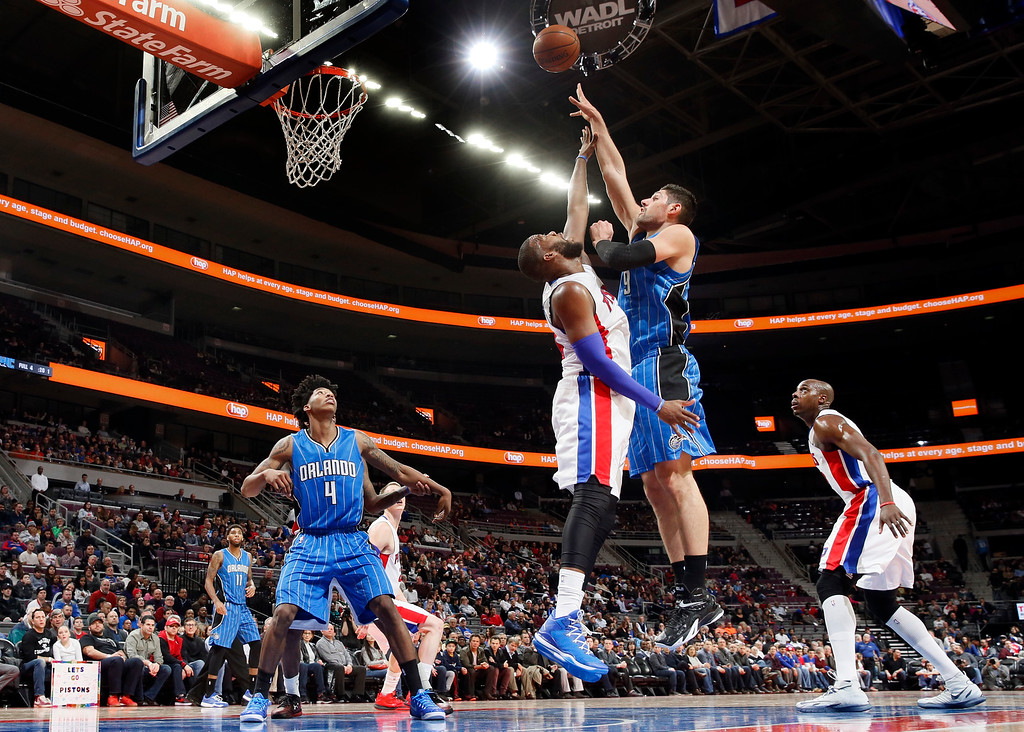 . Orlando Magic center Nikola Vucevic (9) shoots against Detroit Pistons forward Greg Monroe, center right, in the first half of an NBA basketball game in Auburn Hills, Mich., Wednesday, Jan. 21, 2015. (AP Photo/Paul Sancya)