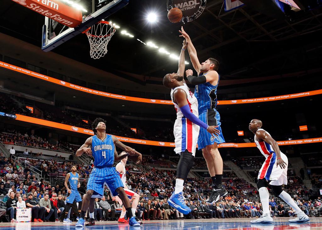 . Orlando Magic center Nikola Vucevic (9) shoots against Detroit Pistons forward Greg Monroe, center right, in the first half of an NBA basketball game in Auburn Hills, Mich., Wednesday, Jan. 21, 2015. (AP Photo/Paul Sancya)