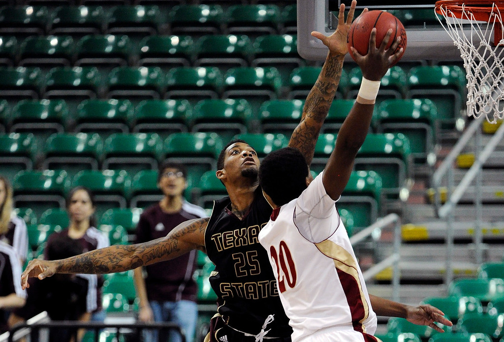 . Texas State\'s Joel Wright (25) blocks a shot from Denver\'s Royce O\'Neale (20) during the fist half of a Western Athletic Conference tournament NCAA college basketball game on Thursday, March 14, 2013, in Las Vegas. (AP Photo/David Becker)