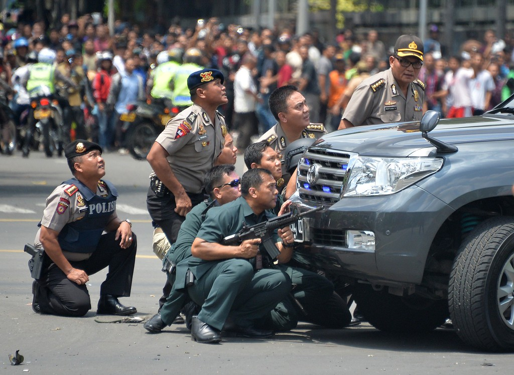 . Indonesian police take position behind a vehicle as they pursue suspects after a series of blasts hit the Indonesia capital Jakarta on January 14, 2016. A series of bombs killed at least three people in the Indonesian capital Jakarta on January 14, with shots fired outside a cafe as police moved in, an AFP journalist at the scene said.     AFP PHOTO / Bay ISMOYOBAY ISMOYO/AFP/Getty Images