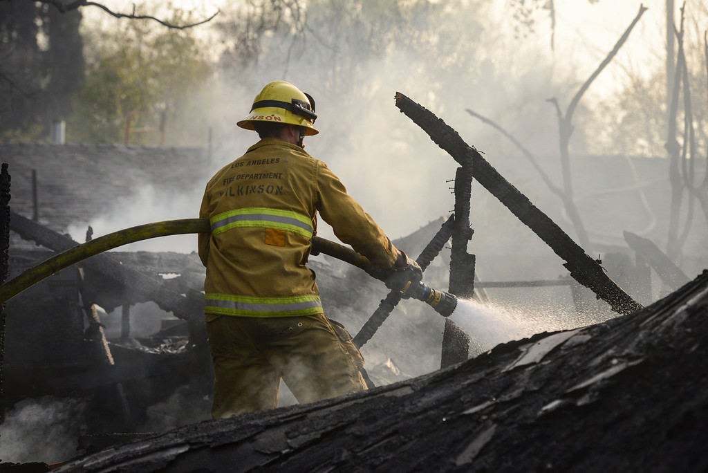 . Firefighters work to put out hot spots on a fire which burned multiple structures on Noble Avnue in North Hills just south of Nordoff street on Thursday, January 23, 2014 ( Photo by David Crane/Los Angeles Daily News )