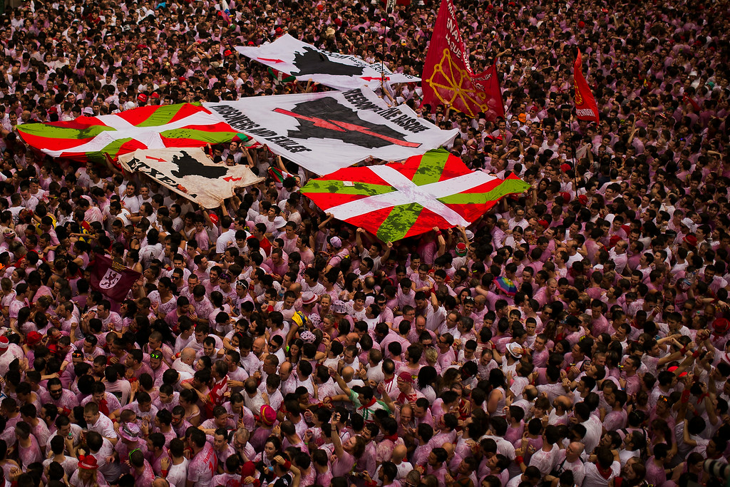 """. Revelers hold a Basque pro independence flag and a banner reading \""""Freedom for the Basques, prisoners and exiles\"""" after the launch of the \'Chupinazo\' rocket, to celebrate the official opening of the 2014 San Fermin fiestas, in Pamplona, Spain, Sunday, July 6, 2014. Revelers from around the world turned out here to kick off the festival with a messy party in the Pamplona town square, one day before the first of eight days of the running of the bulls glorified by Ernest Hemingway\'s 1926 novel \""""The Sun Also Rises.\"""" (AP Photo/Andres Kudacki)"""