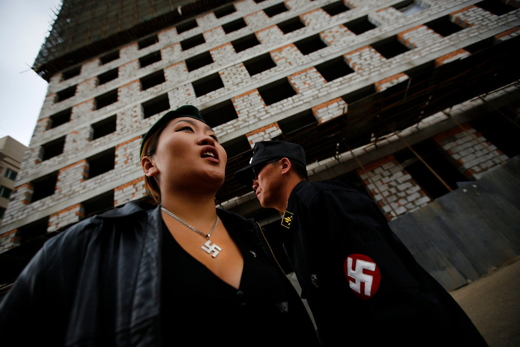 . Ariunbold and Uranjargal (L), leaders of the Mongolian neo-Nazi group Tsagaan Khass, stand next to a construction site in Ulan Bator June 22, 2013. The group has rebranded itself as an environmentalist organisation fighting pollution by foreign-owned mines, seeking legitimacy as it sends Swastika-wearing members to check mining permits. Over the past years, ultra-nationalist groups have expanded in the country and among those garnering attention is Tsagaan Khass, which has recently shifted its focus from activities such as attacks on women it accuses of consorting with foreign men to environmental issues, with the stated goal of protecting Mongolia from foreign mining interests. This ultra-nationalist group was founded in the 1990s and currently has 100-plus members. Picture taken June 22, 2013. REUTERS/Carlos Barria
