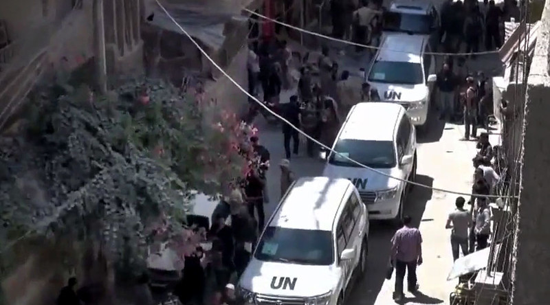 . In this image taken from video obtained from the Shaam News Network, which has been authenticated based on its contents and other AP reporting, Syrians welcome the UN investigation team in Damascus countryside, Syria, on Wednesday, Aug. 28, 2013. (AP Photo/Shaam News Network via AP video)