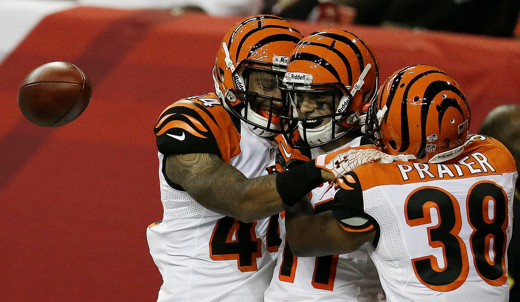 . Cincinnati Bengals safety Tony Dye, left and Cincinnati Bengals cornerback Shaun Prater (38) celebrate Cincinnati Bengals wide receiver Dane Sanzenbacher (11) touchdown after Sanzenbacher  ran a 71-yard punt return into the end zone against the Atlanta Falcons during the second half of a preseason NFL football game, Thursday, Aug. 8, 2013, in Atlanta.  (AP Photo/David Goldman)