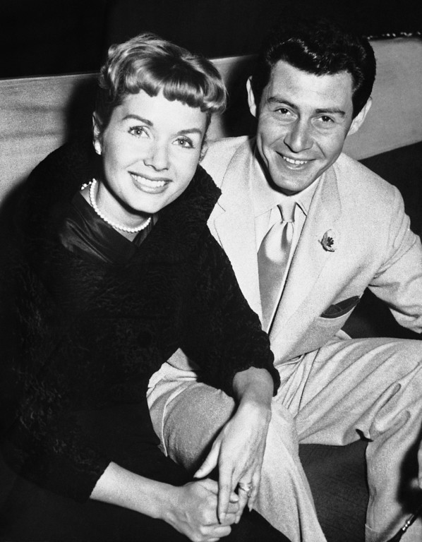 """. File- This June 4, 1957, file photo shows Eddie Fisher and his wife Debbie Reynolds attending the reception at the Prince of Wales Theater, London. Reynolds herself has likened their split to the Jennifer Aniston-Angelina Jolie-Brad Pitt triangle, telling Vanity Fair last year: \""""My three husbands all left me for another woman and obviously I wasn\'t a very sexual lady.\""""  (AP Photo/File)"""