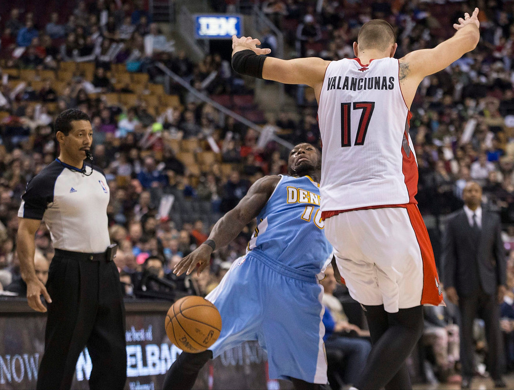 . Denver Nuggets\' Nate Robinson, center, is fouled by Toronto Raptors\' Jonas Valanciunas during the second half of an NBA basketball game on Sunday, Dec. 1, 2013, in Toronto. (AP Photo/The Canadian Press, Chris Young)