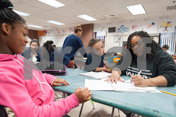 01/11/18 Wesley Bunnell | Staff 45 students from Slade Middle School participate in an American Savings Foundation funded program through the YWCA for youth development opportunities. Activities involve homework, social programs and team building activities. Liel Ayizano, L, sits with Katerina Evans, middle, as YWCA worker Genese Simmons checks off their notebooks for good behavior and attendance to quality for a field trip to Flight Trampoline Park.