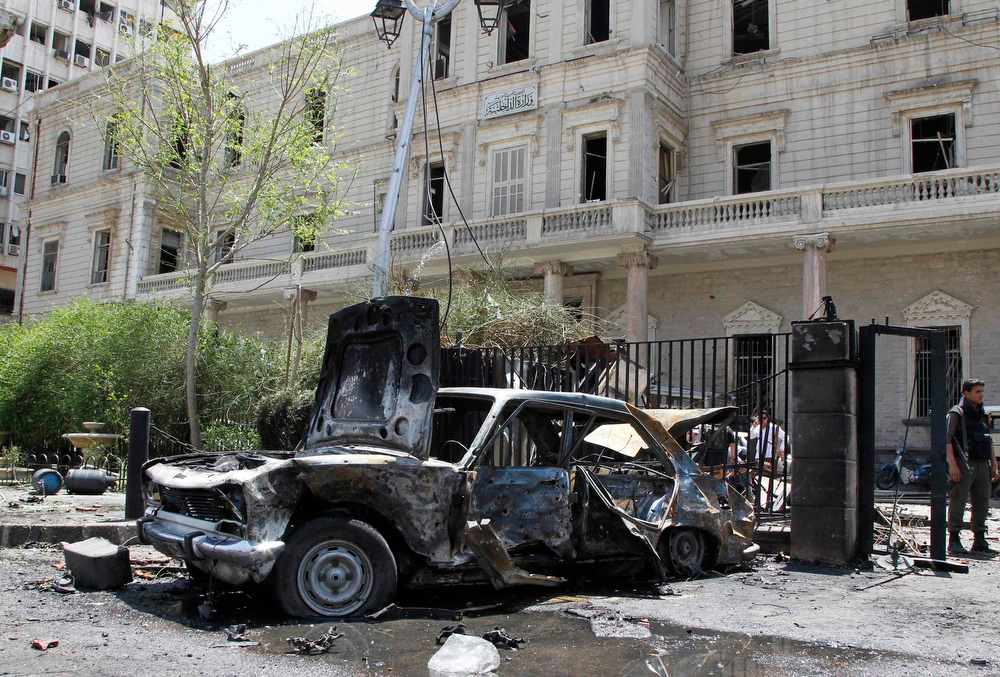 . A destroyed car is pictured near the former Interior Ministry building after a blast at Marjeh Square in Damascus April 30, 2013. The bomb in central Damascus killed 13 people on Tuesday, state television said, a day after Prime Minister Wael al-Halki survived an attack on his convoy in the heart of the Syrian capital. State television said 70 people were wounded, several critically. The British-based Syrian Observatory reported 9 dead civilians and 3 security men and said the death toll was likely to rise.   REUTERS/Khaled al-Hariri