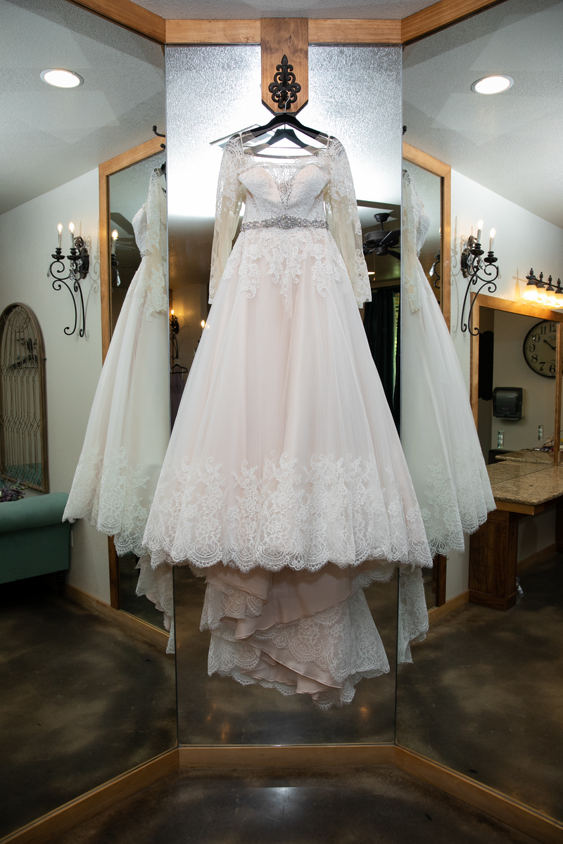 white and pink lace wedding dress with a silver faux belt hanging from a hook surrounded by dressing mirrors