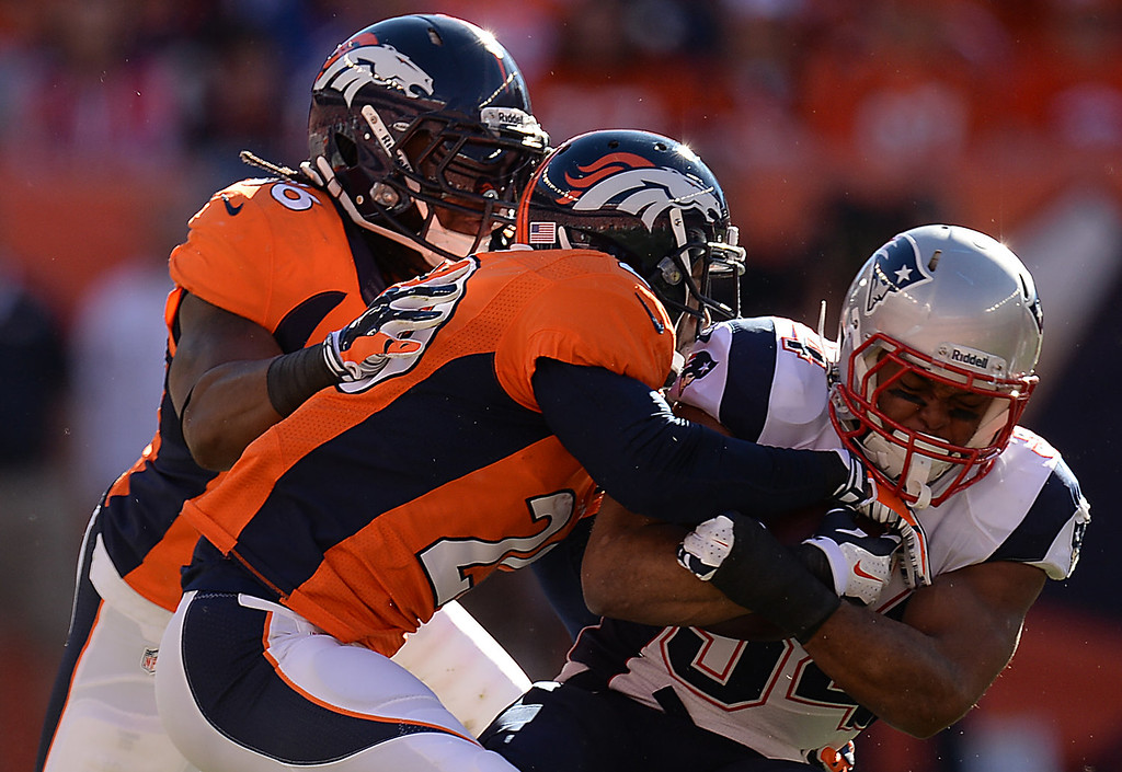 Description of . New England Patriots running back Shane Vereen (34) is tackled by Denver Broncos free safety Mike Adams (20) and Denver Broncos outside linebacker Nate Irving (56) in the first quarter. The Denver Broncos take on the New England Patriots in the AFC Championship game at Sports Authority Field at Mile High in Denver on January 19, 2014. (Photo by Hyoung Chang/The Denver Post)