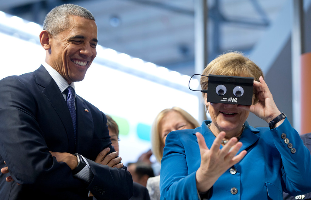 . U.S. President Barack Obama looks on as German Chancellor Angela Merkel tests VR goggles when touring the Hannover Messe,  the world\'s largest industrial technology trade fair, in Hannover, northern Germany, Monday, April 25, 2016. Obama is on a two-day official visit to Germany. (AP Photo/Carolyn Kaster)