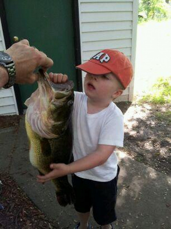 . Garrett Gilbert can\'t possibly hold this 7-pound largemouth bass, the largest ever for his father, David,who hooked the fish on Rush lake this summer. (Courtesy David Gilbert)