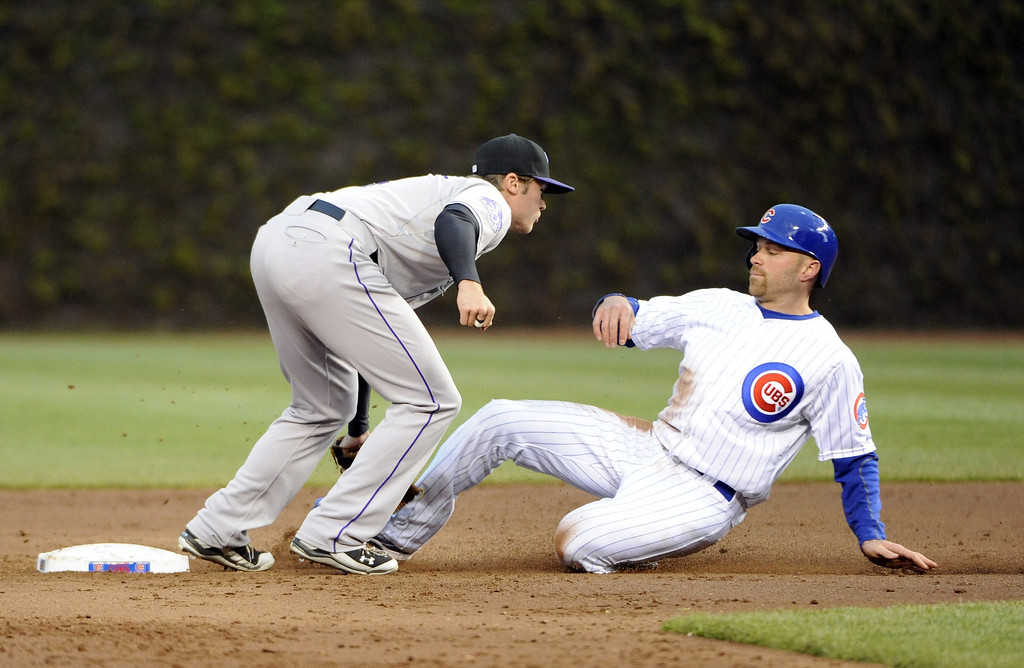 . Nate Schierholtz #19 of the Chicago Cubs is tagged out by Josh Rutledge #14 of the Colorado Rockies on a steal attempt during the first inning on May 13, 2013 at Wrigley Field in Chicago, Illinois.   (Photo by David Banks/Getty Images)