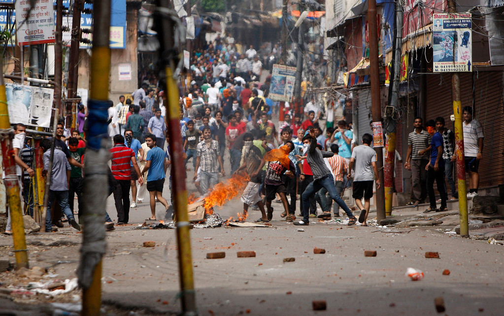 . Indian Hindu protesters throw stones at policemen during a protest after rival communities clashed in Kishtwar, in Jammu, India, Saturday, Aug. 10,2013. Indian forces fired warning shots Saturday to enforce a curfew and to push angry people back into their homes in Kishtwar, in the Indian portion of Kashmir where clashes between Muslims and Hindus during Eid celebrations killed at least two people and injured another 24.(AP Photo/Channi Anand)