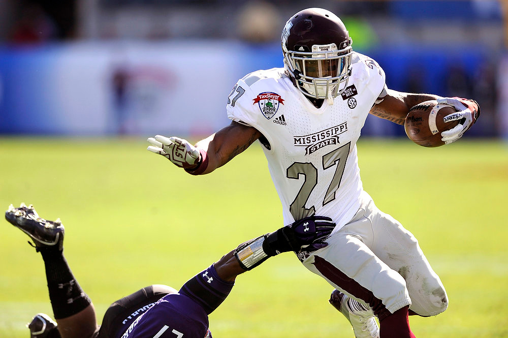 . Mississippi State running back LaDarius Perkins (27) eludes a tackle by Northwestern safety Jared Carpenter (27) during the first half of an NCAA college football game against Northwestern, Tuesday, Jan. 1, 2013, in Jacksonville, Fla. (AP Photo/Stephen Morton)