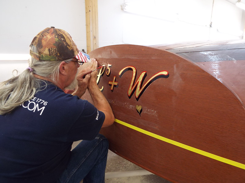 Outlining the transom lettering.
