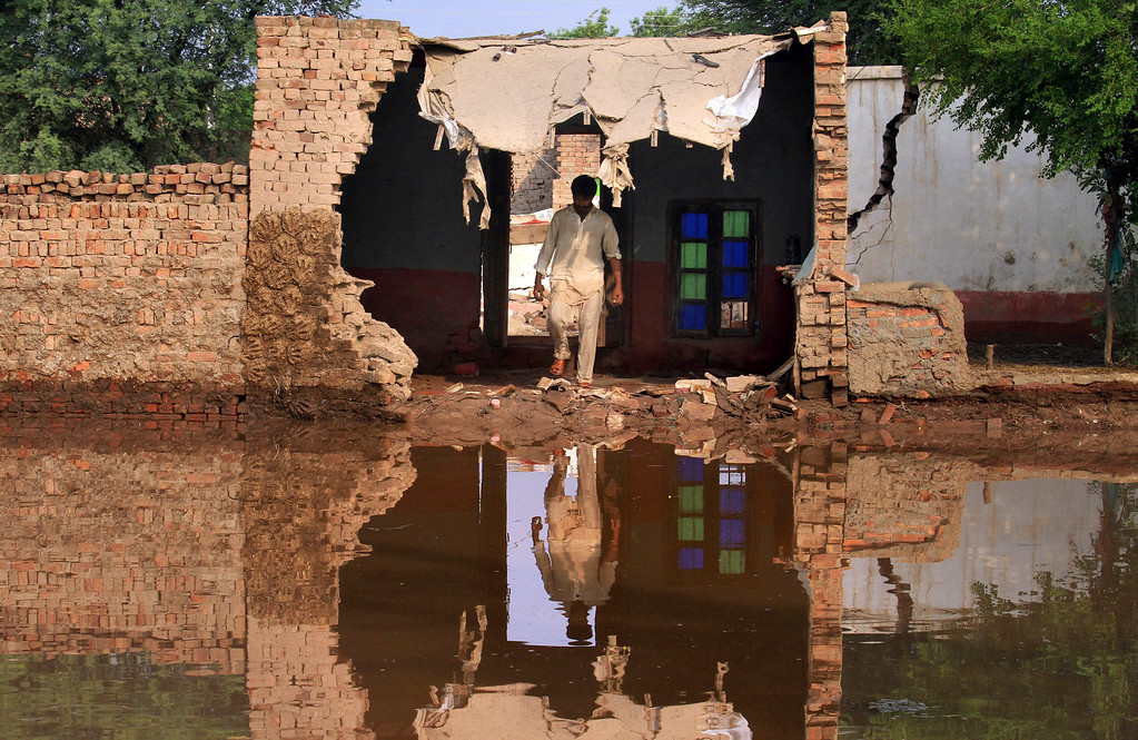 . A Pakistani villager surveys his partially damaged and flooded house in a suburb of Jhang district, 260 kilometers (161 miles) northwest of Lahore, Pakistan, Wednesday, Sept. 10, 2014.  (AP Photo/K.M. Chaudary)