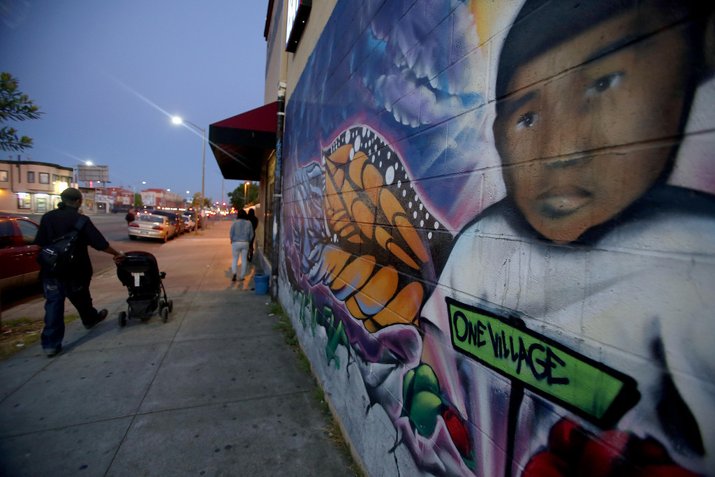 """. A man and his child pass a mural depicting Carlos \""""Carlitos\"""" Nava along International Boulevard near 64th Avenue in Oakland, Calif., on Wednesday, April 17, 2013. Carlitos, 3, was killed in a drive-by shooting on the site in 2011. Oakland Tribune reporter Scott Johnson will be living in East Oakland for one month to chronicle what it\'s like to live near a high crime area. The boundaries for the project are 55th to 64th Avenues between Foothill and International and Foothill Boulevards. (Jane Tyska/Staff)"""