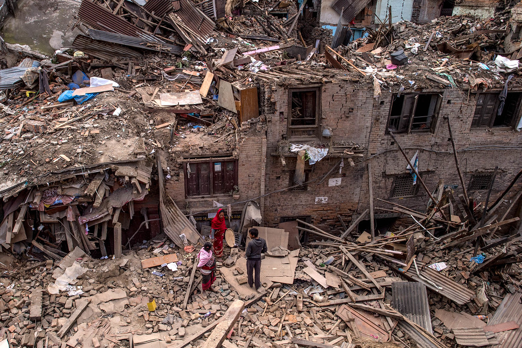 . Nepalese earthquake victims walk among debris of collapsed buildings on April 29, 2015 in Bhaktapur, Nepal. A major 7.8 earthquake hit Kathmandu mid-day on Saturday, and was followed by multiple aftershocks that triggered avalanches on Mt. Everest that buried mountain climbers in their base camps. Many houses, buildings and temples in the capital were destroyed during the earthquake, leaving over 5000 dead and many more trapped under the debris, as emergency rescue workers attempt to clear debris and find survivors. Regular aftershocks have hampered recovery missions as locals, officials and aid workers attempt to recover bodies from the rubble.  (Photo by David Ramos/Getty Images)