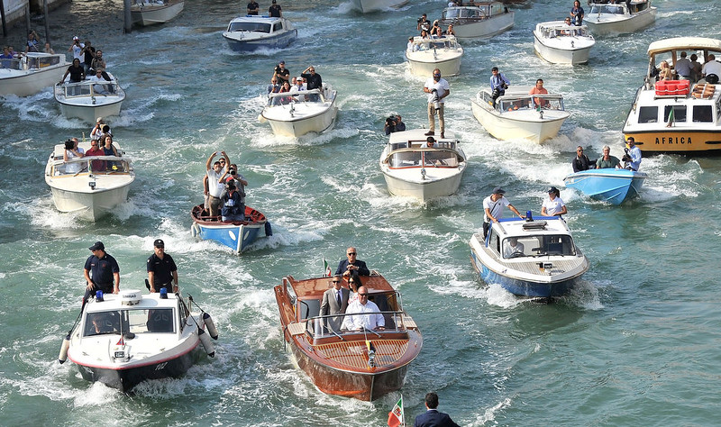 . The boat, center front, carrying George Clooney and his new wife Amal Alamuddin is surrounded by media and security boats as they cruise the Grand Canal after leaving the Aman luxury Hotel in Venice, Italy, Sunday, Sept. 28, 2014. George Clooney married human rights lawyer Amal Alamuddin Saturday, the actor\'s representative said. (AP Photo/Luigi Costantini)