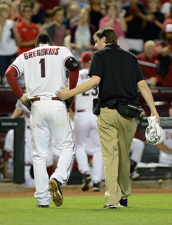 . PHOENIX, AZ - APRIL 26:  Didi Gregorius #1 of the Arizona Diamondbacks is escorted back to the dugout after being hit in the head by a pitch from Josh Outman (not pictured) of the Colorado Rockies in the seventh inning at Chase Field on April 26, 2013 in Phoenix, Arizona.  (Photo by Jennifer Stewart/Getty Images)