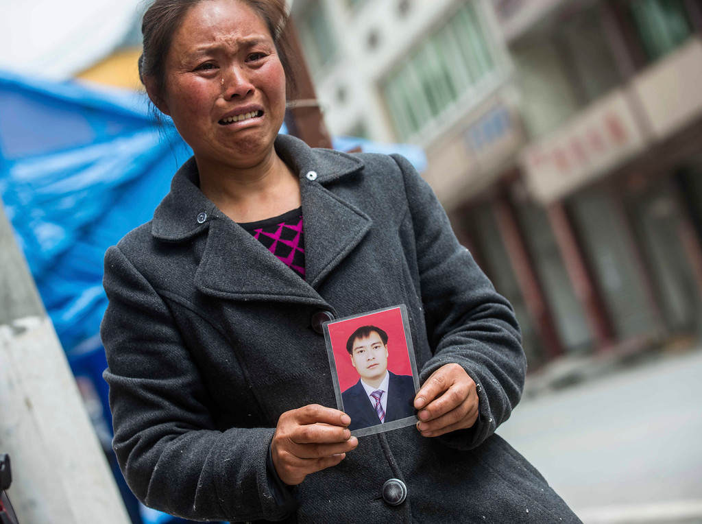 . This photo taken on April 24, 2013 shows a photo of Huang Zongxue-- who died during the earthquake---- held in his sister\'s hands in Ya\'an, in southwest China\'s Sichuan province. The April 20 earthquake killed at least 193 people and injured more than 12,000, and left tens of thousands of homeless survivors living in makeshift tents or on the streets, facing shortages of food and supplies.  AFP/Getty Images