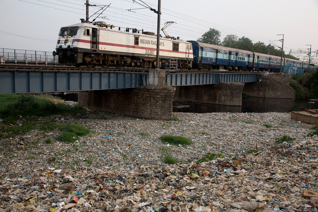 ". A train runs over the garbage choked the Hussain sagar lake in Hyderabad, India, Monday, June 4, 2018. The theme for this year\'s World Environment Day, marked on June 5, is ""Beat Plastic Pollution.\"" (AP Photo/Mahesh Kumar A.)"
