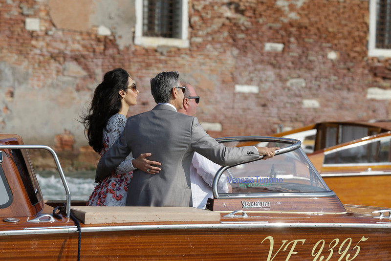 . George Clooney smiles to his wife Amal Alamuddin as they cruise the Grand Canal after leaving the Aman luxury Hotel in Venice, Italy, Sunday, Sept. 28, 2014. George Clooney married human rights lawyer Amal Alamuddin Saturday, the actor\'s representative said, out of sight of pursuing paparazzi and adoring crowds. (AP Photo/Luca Bruno)