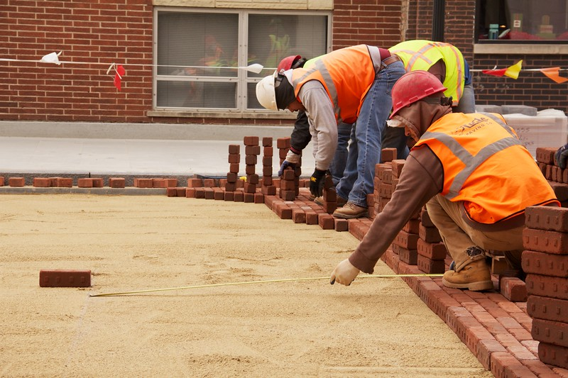 Construction workers lay paving bricks while another takes a measurement during Marion Street reconstruction project on Saturday November 19, 2011 in Oak Park, Illinois,  USA.  Brick is being used to return the street to its early 20th century appearance and reduce storm runoff.