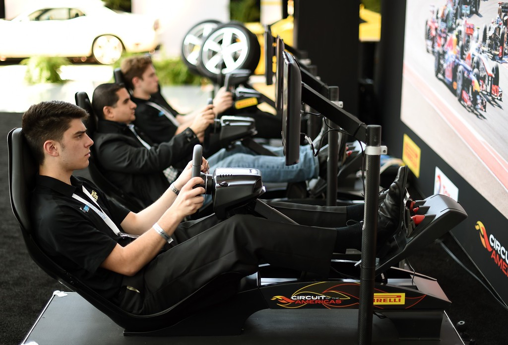 . Men try out Pirelli driving simulators during the second press preview day at the 2014 New York International Auto Show  April 17, 2014  in New York at the Jacob Javits Center. AFP PHOTO / Timothy A. CLARY/AFP/Getty Images