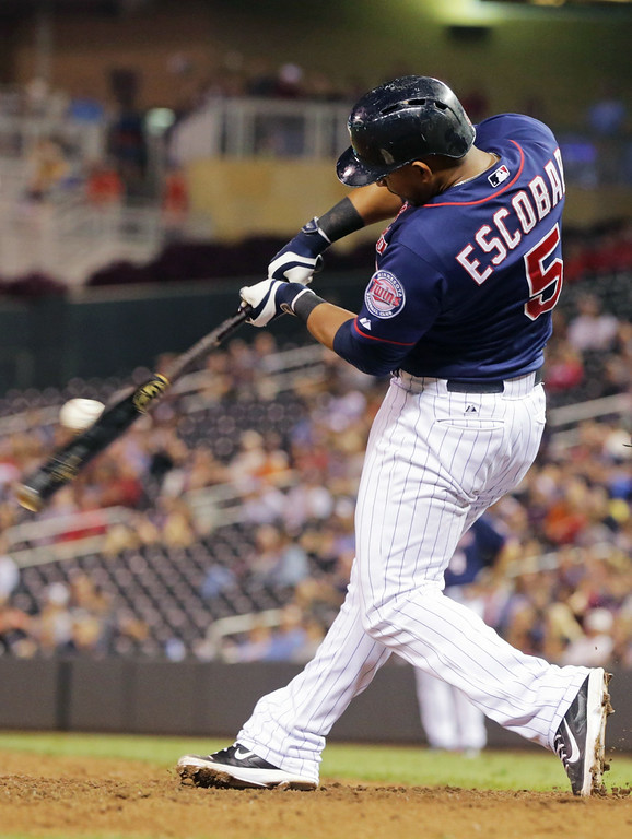 . Minnesota Twins\' Eduardo Escobar hits a single off Detroit Tigers pitcher Joba Chamberlain in the seventh inning of a baseball game, Friday, Aug. 22, 2014, in Minneapolis. Escobar went 5-for-6 at the plate, including a two-run home run in the second. The Twins won 20-6. (AP Photo/Jim Mone)
