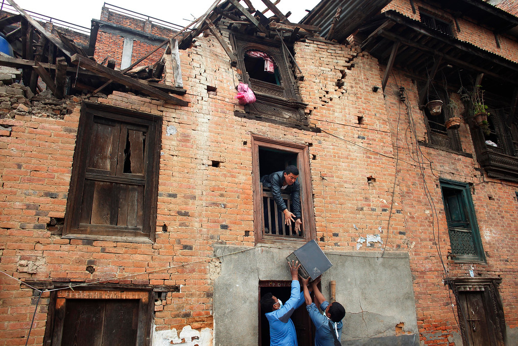 . Nepalese earthquake-affected victims salvage belongings from a damaged house in Lalitpur, on the outskirts of Kathmandu, Nepal, Thursday, April 30, 2015. In mere seconds, Saturday\'s earthquake devastated a swathe of Nepal. Three of the seven World Heritage sites in the Kathmandu Valley have been severely damaged, including Durbar Square with pagodas and temples dating from the 15th to 18th centuries, according to UNESCO, the United Nations cultural agency. (AP Photo/Niranjan Shrestha)