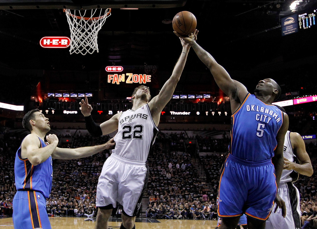 . Tiago Splitter #22 of the San Antonio Spurs goes up for a rebound against Kendrick Perkins #5 of the Oklahoma City Thunder in the first half in Game One of the Western Conference Finals during the 2014 NBA Playoffs at AT&T Center on May 19, 2014 in San Antonio, Texas.  (Photo by Chris Covatta/Getty Images)