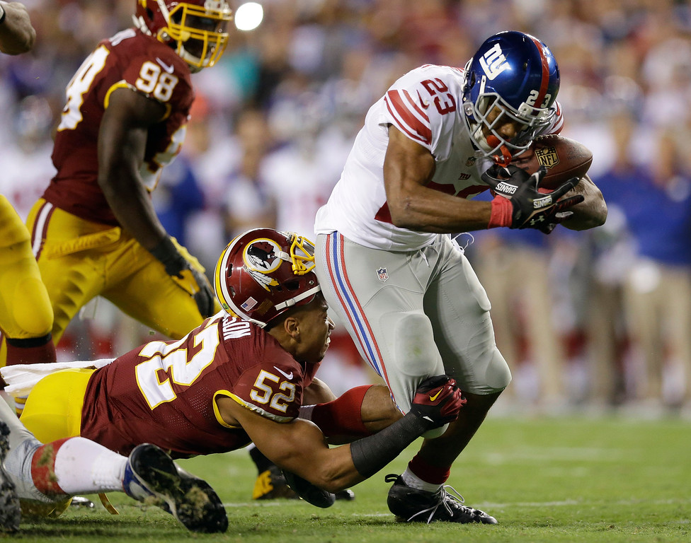. Washington Redskins inside linebacker Keenan Robinson (52) loses his helmet as he tries to stop New York Giants running back Rashad Jennings (23) during the first half of an NFL football game in Landover, Md., Thursday, Sept. 25, 2014. (AP Photo/Patrick Semansky)