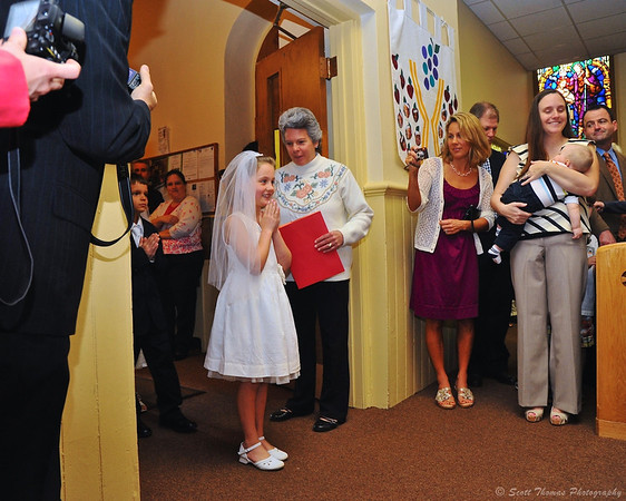 A girl pauses before walking into church for her First Communion ceremony at St. Francis Xavier Church in Marcellus, New York.