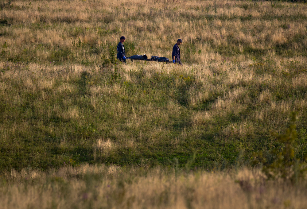. Emergency workers carry the body of a victim at the crash site of Malaysia Airlines Flight 17 near the village of Hrabove, eastern Ukraine, Saturday, July 19, 2014. World leaders demanded Friday that pro-Russia rebels who control the eastern Ukraine crash site of Malaysia Airlines Flight 17 give immediate, unfettered access to independent investigators to determine who shot down the plane. (AP Photo/Vadim Ghirda)