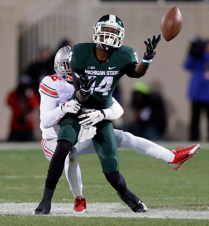 . Michigan State wide receiver Tony Lippett (14) loses control of the ball after a hit by Ohio State cornerback Doran Grant (12) during the first half of an NCAA college football game in East Lansing, Mich., Saturday, Nov. 8, 2014. (AP Photo/Carlos Osorio)