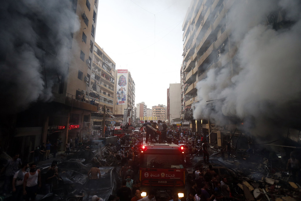 . Lebanese civilians and emergency personnel gather at the site of a car bomb between the Bir el-Abed and Roueiss neighborhoods, in the southern suburb of Beirut on August 15, 2013. A powerful car bomb killed at least six people and more than 100 wounded in a Beirut stronghold of Shiite movement Hezbollah, an army source and Lebanese Red Cross said.   STR-/AFP/Getty Images