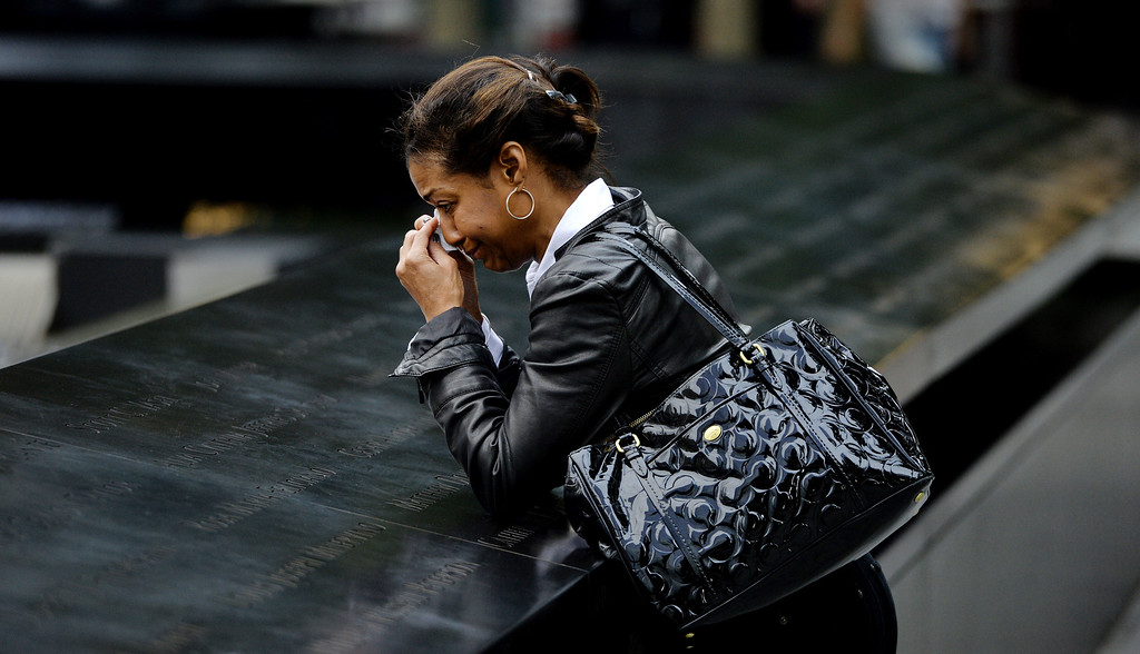 . A woman pauses at the edge of the North Pool during memorial observances on the 13th anniversary of the Sept. 11 terror attacks on the World Trade Center in New York, Thursday, Sept. 11, 2014.   (AP Photo/Justin Lane, Pool)