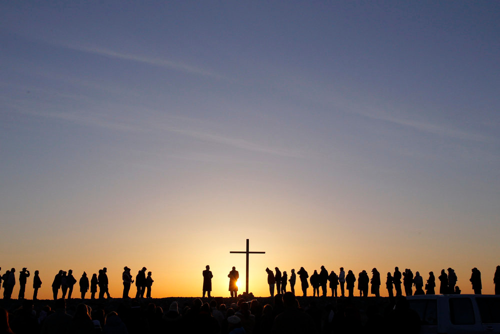 Description of . People are silhouetted as the sun rises during an Easter sunrise service in Scituate, Massachusetts March 31, 2013.  REUTERS/Jessica Rinaldi