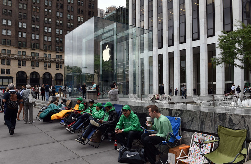 """. People wait in line on chairs September 9, 2014 outside the Apple Store on 5th Avenue in New York. Tech trend-setter Apple charts its future course Tuesday amid expectations for new big-screen iPhones and possibly an \""""iWatch\"""" which could shake up the world of wearable computing. Apple has maintained its customary arch silence, but a frenzy of speculation suggests a push into a new segment as it seeks to broaden the appeal of its iconic iPhone. DON EMMERT/AFP/Getty Images"""